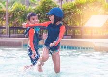 兄弟姐妹是跑和追逐在游泳场 库存图片