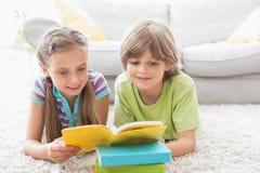 兄弟姐妹阅读书,当说谎在地毯时 免版税库存照片