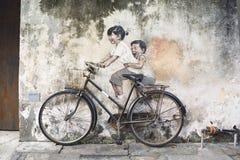 兄弟姐妹骑自行车者街道艺术壁画在乔治城,槟榔岛,马来西亚 库存照片