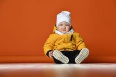 兄弟子项给愉快的一个姐妹微笑的二冬天穿衣 在下来夹克的孩子 免版税库存照片