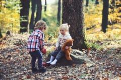 兄弟投入红色起动的帮助姐妹 小男孩在女孩脚上把鞋子放 帮手概念 准备好的孩子 免版税图库摄影