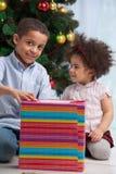兄弟拿着姐妹的圣诞节礼品 库存图片
