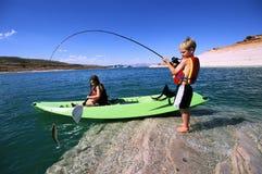 兄弟捕鱼划皮船的姐妹 图库摄影