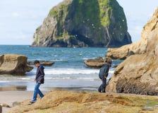兄弟探索tidepools在海角Kiwanda 库存照片