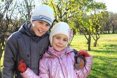 兄弟,姐妹在结构树附近拥抱 免版税库存照片