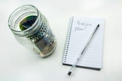 充分一个玻璃瓶子的照片的关闭南非金钱、一支笔和笔记薄有简单的背景 库存图片