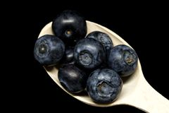 充分一把木匙子的宏指令在黑背景的成熟蓝莓 新鲜的成熟水多的越桔 库存照片