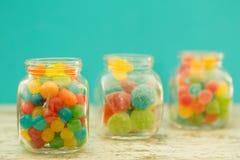 充分三个玻璃瓶子豆形软糖有蓝色背景 免版税图库摄影