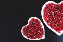 充分两块白色心形的板材新鲜的水多的石榴种子、一点匙子,整个果子和成熟一个 定调子 免版税库存照片