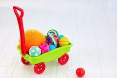 充分五颜六色的玩具台车孩子` s发展的不同的颜色和形状有触觉的球 免版税库存照片