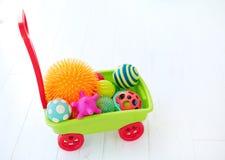 充分五颜六色的玩具台车孩子` s发展的不同的颜色和形状有触觉的球 免版税库存图片