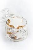 充分关闭一个玻璃瓶子用在白色蓬松背景的圣诞节自创星曲奇饼 免版税图库摄影