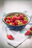 充分关闭蓝色金属碗在白色木土气背景的新鲜的草莓 免版税库存照片