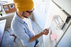 充分写下想法的年轻创造性的人在墙壁稠粘的笔记 免版税库存照片