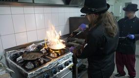 充分加在平底锅的男性厨师酒肉和素食者混合在烹调一鲜美flambe的餐馆厨房里 股票录像