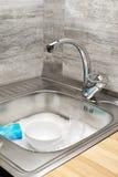 充分厨房水槽泡沫、碗筷和蓝色清洁海绵 免版税库存图片