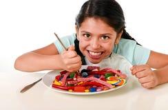 充分吃盘糖果的愉快的拉丁女孩和gummies与叉子和刀子和大可乐瓶在糖恶习 库存照片