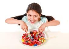 充分吃盘糖果的愉快的拉丁女孩和gummies与叉子和刀子和大可乐瓶在糖恶习 免版税库存图片