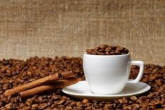 充分咖啡杯咖啡豆和肉桂条 免版税库存图片