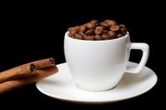 充分咖啡杯咖啡豆和肉桂条 库存图片