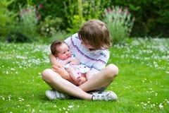 充分坐在一个美丽的夏天庭院里的逗人喜爱的男孩有拿着他新出生的姐妹的花的 免版税库存图片