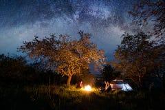 充分坐在营火的三个游人在帐篷在树下和美丽的夜空星和银河附近 免版税库存图片