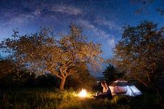 充分坐在营火的浪漫夫妇游人在帐篷在树下和美丽的夜空星和银河附近 免版税库存图片