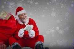 充分坐由大袋的圣诞老人的综合图象计数货币笔记的礼物 库存照片