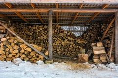 充分堆木材的棚切好的木柴在冬天 免版税库存照片