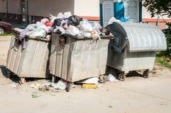 充分大两个金属大型垃圾桶垃圾箱污染街道的溢出废弃物和破烂物在城市 图库摄影