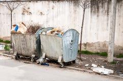 充分大两个金属大型垃圾桶垃圾箱污染街道的溢出废弃物在城市 库存照片