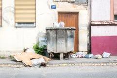 充分大两个金属大型垃圾桶垃圾箱污染街道的溢出废弃物在有破烂物的城市 库存图片