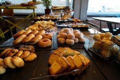 充分希腊早餐自助餐桌以酥皮点心,小圆面包,薄煎饼,油炸圈饼,黄油蛋糕,薄饼,饼品种,煮沸了鸡蛋等等 库存图片
