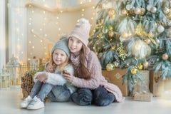 充分庆祝接近xmas树的两个逗人喜爱的令人敬畏的女孩姐妹新年圣诞节在时髦的礼服的玩具用糖果 库存图片