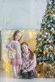 充分庆祝接近xmas树的两个逗人喜爱的令人敬畏的女孩姐妹新年圣诞节在时髦的礼服的玩具用糖果 免版税库存照片