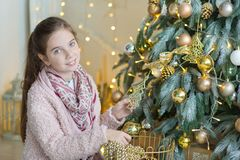 充分庆祝接近xmas树的逗人喜爱的令人敬畏的女孩新年圣诞节在时髦的礼服的玩具用糖果 库存照片