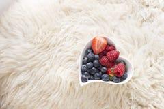 充分心形的碗莓果和身分在绵羊皮肤从顶视图 免版税库存图片
