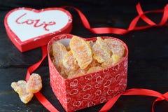 充分心形的箱子糖煮的橙色切片 在心脏,在黑背景的红色丝带形状的盒盖与爱词的 库存照片