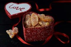 充分心形的箱子糖煮的橙色切片 在心脏,在黑背景的红色丝带形状的盒盖与爱词的 免版税库存照片