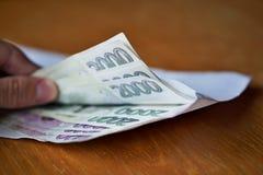 充分打开一个白色信封捷克货币(捷克冠, CZK, Kc)的男性手在木桌上作为现金调动的标志 免版税库存照片
