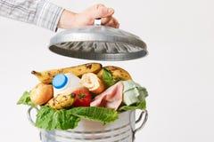 充分把盒盖放的手在垃圾箱浪费的食物上 库存照片