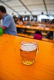 充分抢劫与泡沫的啤酒在一张木桌上 库存图片