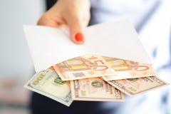 充分拿着和通过一个白色信封金钱的妇女手建议洗钱,非法现金调动和贿赂 免版税库存照片