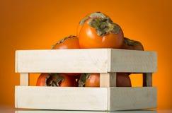 充分木箱在橙色背景的成熟柿子果子 免版税图库摄影