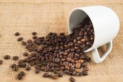 充分杯在黑森州的布料的咖啡豆 免版税库存照片