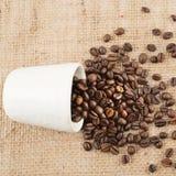 充分杯在黑森州的布料的咖啡豆 免版税库存图片