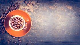 充分浓咖啡杯子在土气木背景,顶视图的咖啡豆 图库摄影