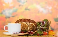 充分烘干在篮子、碗野玫瑰果,杯、茶碟和匙子的橙色切片在木桌上 库存照片