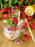 充分玻璃水罐冰块、莓果、柠檬切片和薄菏 库存图片