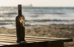 充分瓶在海滩的沙子 库存照片